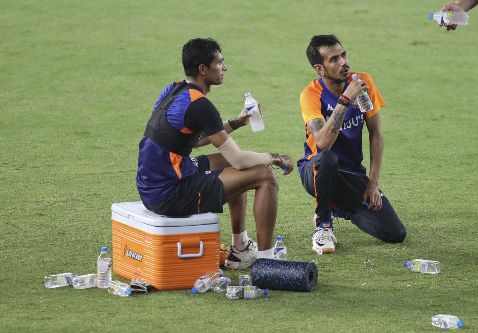 India's Navdeep Saini, left, and Y Chahal take a water break during a training session ahead of the first Twenty20 cricket match between India and England in Ahmedabad, India, Tuesday, March 9, 2021. (AP Photo/Aijaz Rahi)