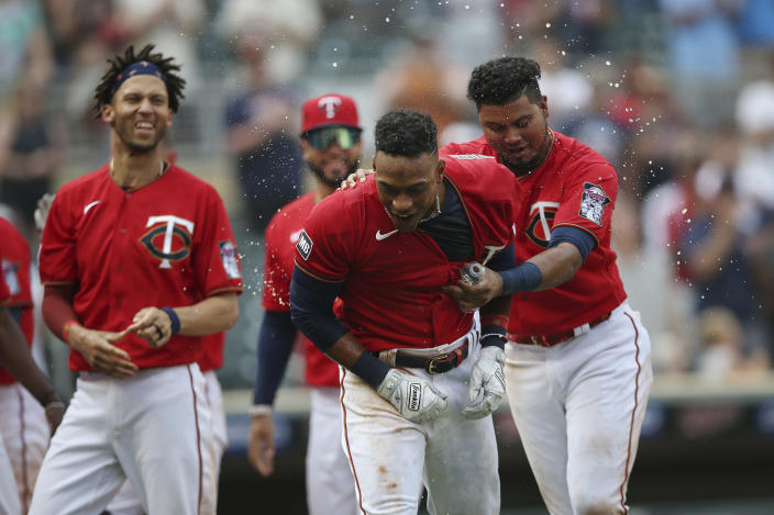 Minnesota Twins' Jorge Polanco, center, celebrates with teammates after hitting a home run to win the game against the Detroit Tigers during the 10th inning of a baseball game Sunday, July 11, 2021, in Minneapolis. (AP Photo/Stacy Bengs)