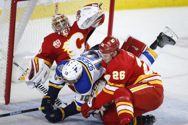 St. Louis Blues' Brayden Schenn, center, is checked into Calgary Flames goalie David Rittich, left, by Michael Stone during the second period of an NHL hockey game in Calgary, Saturday, Nov. 9, 2019. (Jeff McIntosh/The Canadian Press via AP)