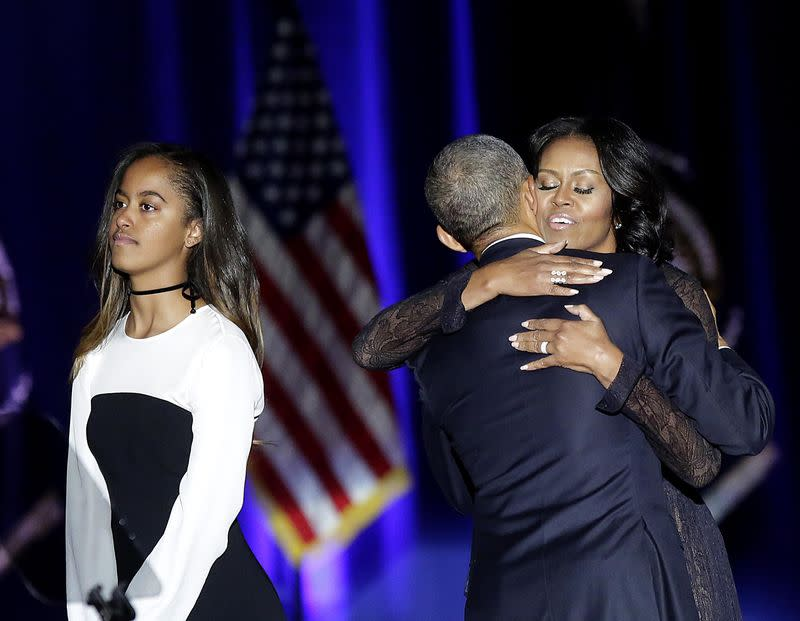 Malia on stage with her parents hugging after the president's farewell address