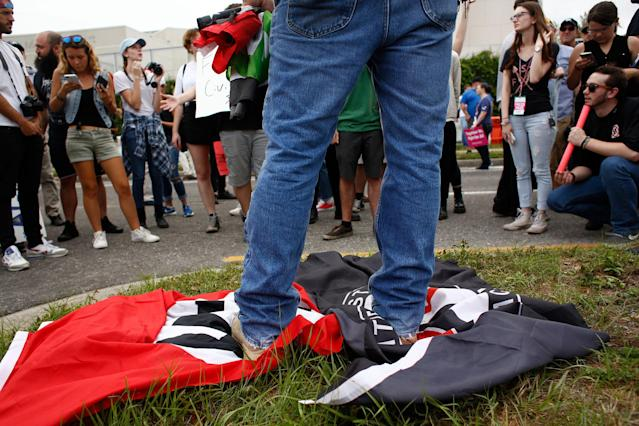 <p>A man stands on a Nazi flag and an ANTIFA flag as demonstrators gather near the site of a planned speech by white nationalist Richard Spencer, who popularized the term 'alt-right', at the University of Florida campus on Oct.19, 2017 in Gainesville, Fla. (Photo: Brian Blanco/Getty Images) </p>