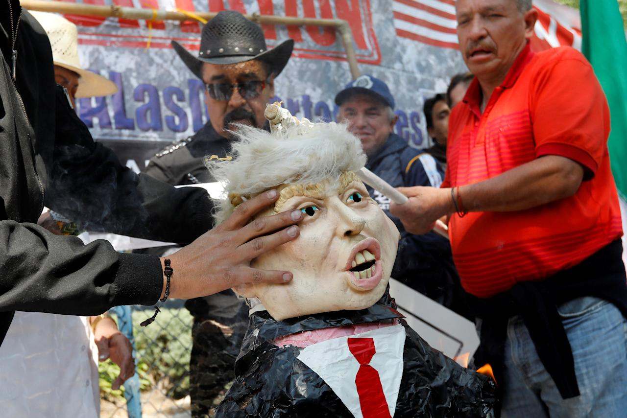 Activists hold a pinata resembling U.S. President Donald Trump as they mark one year anniversary of Trump inauguration with a protest outside the U.S embassy in Mexico City, Mexico January 20, 2018. REUTERS/Carlos Jasso