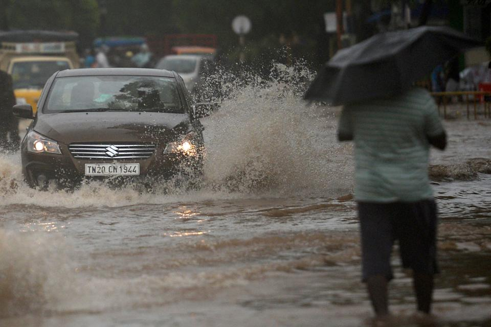 Motorists make their way along a waterlogged road after heavy rains following Cyclone Nivar landfall, in Puducherry on November 26, 2020. (Photo by ARUN SANKAR/AFP via Getty Images)
