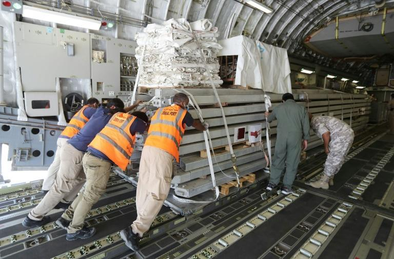 Workers load a plane as Qatar begins sending field hospital and medical aid to Lebanon from the al-Udeid airbase on August 5, 2020 on the outskirts of Doha (AFP Photo/KARIM JAAFAR)