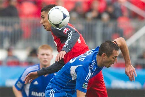 Toronto FC 's Luis Silva, left, battles for the ball with Montreal Impact's Davy Arnaud during first half MLS action in Toronto on Saturday Oct. 20, 2012. (AP Photo/ The Canadian Press, Chris Young)