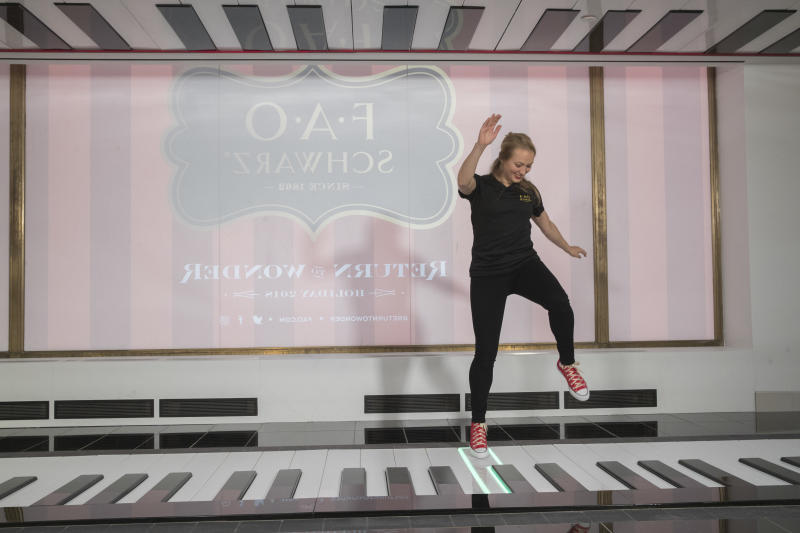 "In this Tuesday, Nov. 13, 2018 photo, an employee plays the FAO Premium Piano Dance Mat during a media preview of the new FAO Schwarz store at Rockefeller Center in New York. Three years after it closed its beloved, fantasy land of a toy store on Fifth Avenue, FAO Schwarz makes its return to New York City. The new version will be smaller, but will have familiar attractions including a musical clock tower and the giant piano keyboard mat on which Tom Hanks danced in the film ""Big."" (AP Photo/Mary Altaffer)"