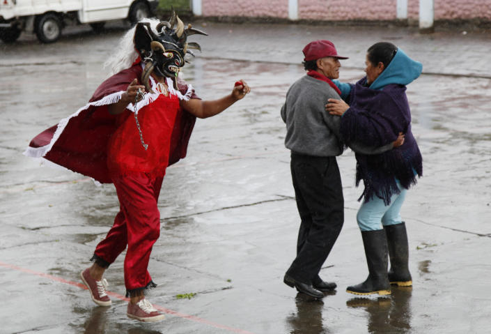 Revelers dance in La Diablada in Pillaro, Ecuador, Monday, Jan. 6, 2014, to celebrate the end of the year and start the new one. The town of Pillaro kicks off the Diablada with neighborhoods competing to bring as many people dressed as different characters. Originally the devil costume was used to open up space to allow other participants to dance, but over the years the character gained popularity and became the soul of the feast. (AP Photo/Dolores Ochoa)