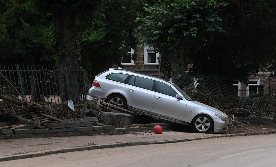 A damaged car, washed away by flood waters sits on some debris in a street in the town of Ahrweiler-Bad Neuenahr on July 15, 2021. - Heavy rains and floods lashing western Europe have killed at least 45 people in Germany and left around 50 missing, as rising waters led several houses to collapse. (Photo by Christof STACHE / AFP) (Photo by CHRISTOF STACHE/AFP via Getty Images)
