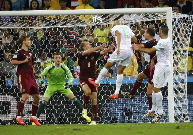 Russia's goalkeeper Igor Akinfeev (2nd L) prepares to save a ball headed by Algeria's Islam Slimani (3rd R) during their 2014 World Cup Group H soccer match at the Baixada arena in Curitiba June 26, 2014. REUTERS/Murad Sezer (BRAZIL - Tags: SOCCER SPORT WORLD CUP TPX IMAGES OF THE DAY)