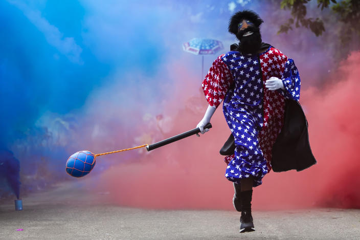 """A member of a """"bate-bola"""" or ball hitters group - men who dress up in exuberant, identical, hand-made costumes known as """"fantasias"""" - runs past during a brief appearance as part of a Carnival tradition despite restrictions due to the new coronavirus pandemic, in Rio de Janeiro, Brazil, Saturday, Feb. 13, 2021. Rio's city government officially suspended Carnival and warns it will have no tolerance for those who try to celebrate with open street parades or clandestine parties. (AP Photo/Bruna Prado)"""