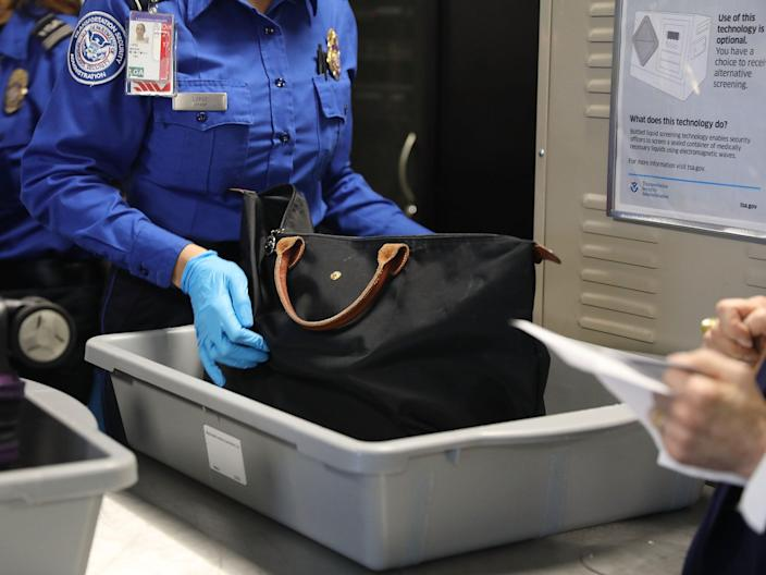<p>A Transportation Security Administration (TSA) worker screens luggage at LaGuardia Airport (LGA) on 26 September 2017 in New York City</p> ((Getty Images))