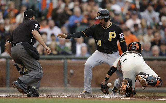 Pittsburgh Pirates' Neil Walker, center, scores past San Francisco Giants catcher Buster Posey, right, in the first inning of a baseball game Monday, July 28, 2014, in San Francisco. Walker scored on a sacrifice fly by Pittsburgh's Gregory Polanco. At left is home plate umpire Jim Reynolds. (AP Photo/Ben Margot)