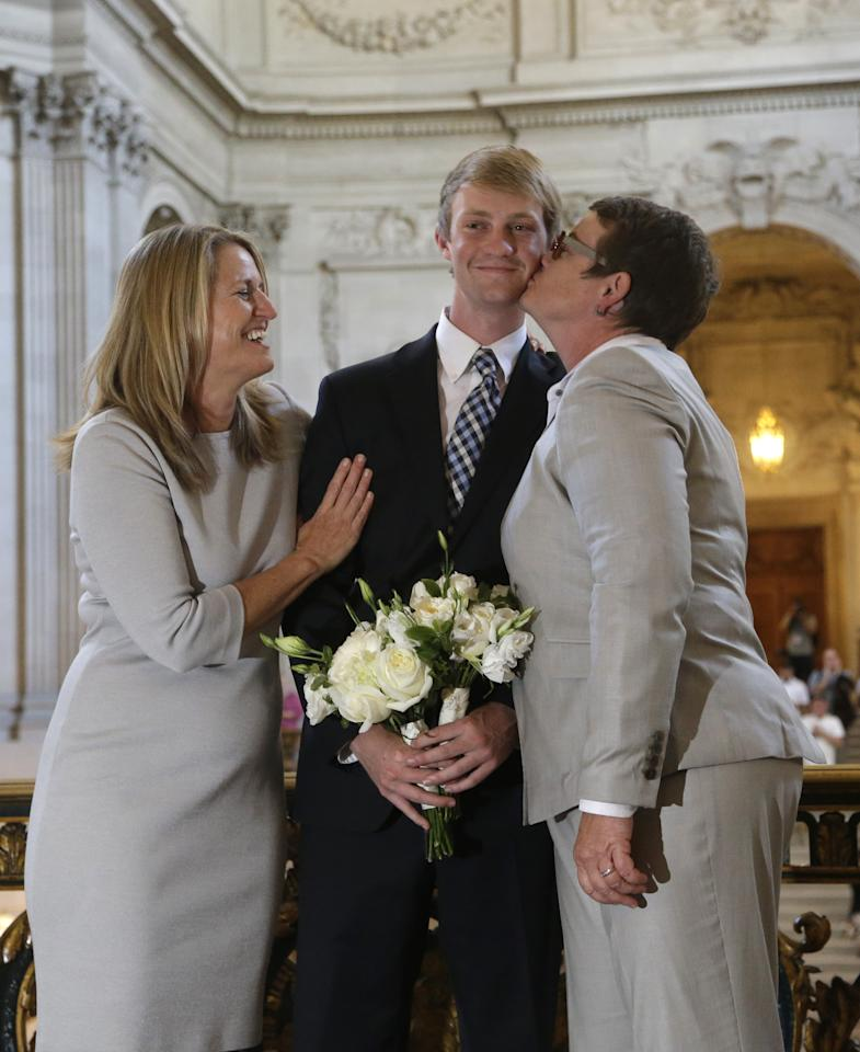 Elliott Perry, center, is kissed by his mother, Kris Perry, after his parents, Sandy Stier, left, and Perry were wed by California Attorney General Kamala Harris at City Hall in San Francisco, Friday, June 28, 2013. Stier and Perry, the lead plaintiffs in the U.S. Supreme Court case that overturned California's same-sex marriage ban, tied the knot about an hour after a federal appeals court freed same-sex couples to obtain marriage licenses for the first time in 4 1/2 years.(AP Photo/Marcio Jose Sanchez)