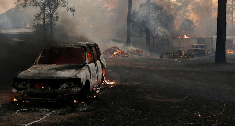 Burning property and car in Possum Brush, south of Taree in the Mid North Coast, on Tuesday.