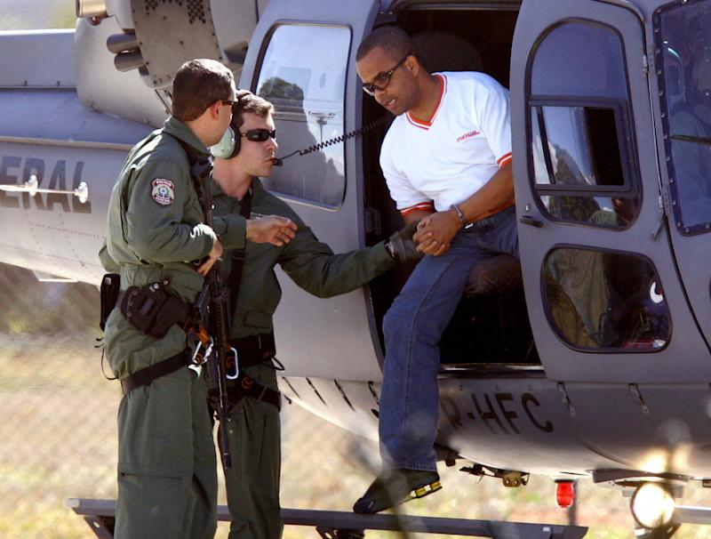 BRASILIA, BRAZIL: Brazilian drug trafficker Fernandinho Beira-Mar (R) disembarks from a helicopter upon his arrival in Brasilia, 22 July, 2005. Beira-Mar was transferred from Sao Paulo after the state governement refused to keep him in the Presidente Bernardes' jail. AFP PHOTO/Evaristo SA (Photo credit should read EVARISTO SA/AFP via Getty Images)