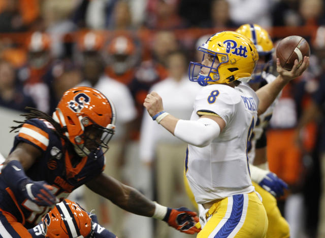 Pittsburgh's Kenny Pickett, right, passes the ball under pressure from Syracuse's Lakiem Williams, left, during the first quarter of an NCAA college football game in Syracuse, N.Y., Friday, Oct. 18, 2019. (AP Photo/Nick Lisi)