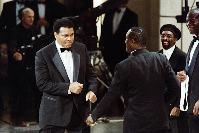 Muhammad Ali (L) pretends to square off against Joe Frazier (3rd R) before Frazier presents Ali with the National Sports Award on June 20, 1993 (AFP Photo/Robert Giroux)