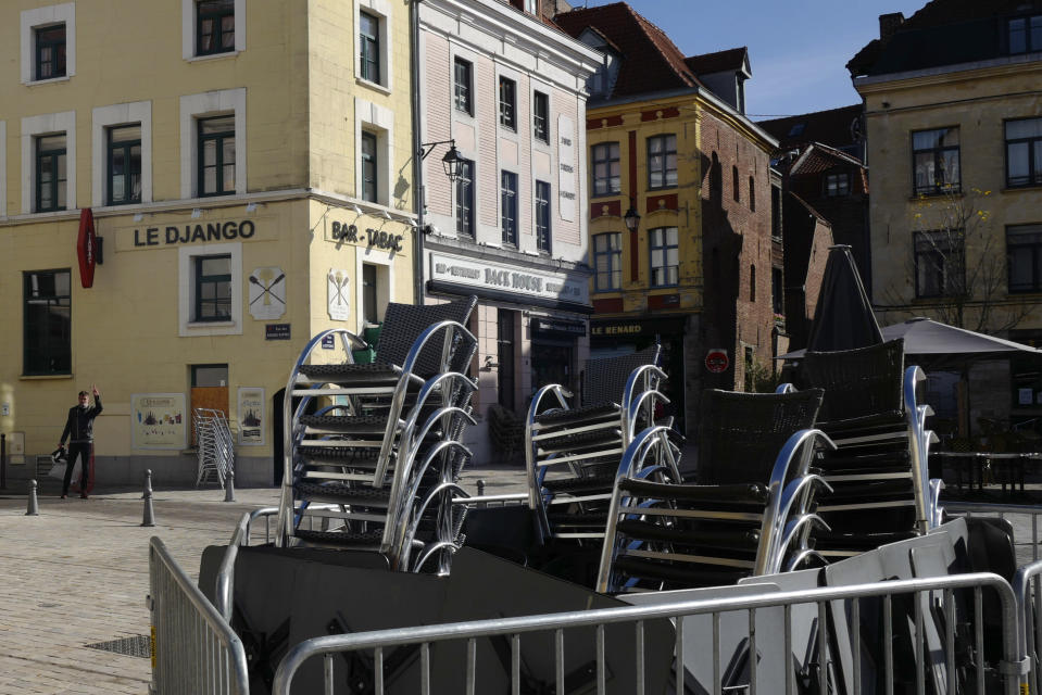 Stacked chairs are seen in front of a cafe in Lille, northern France, Saturday, Oct. 10, 2020. French authorities have placed Lille on maximum virus alert on Monday, banning festive gatherings and requiring all bars to close but allowing restaurants to remain open, as numbers of infections are rapidly increasing. (AP Photo/Michel Spingler)