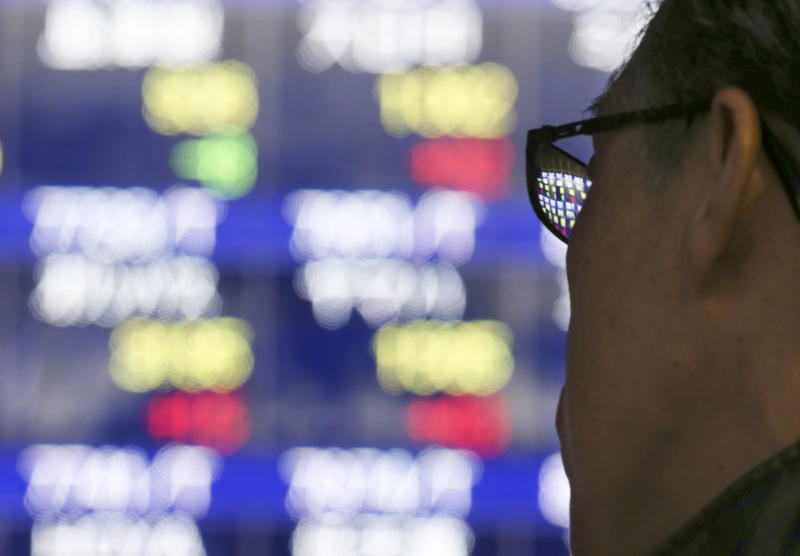A man looks at an electronic stock board of a securities firm in Tokyo, Tuesday, Dec. 17, 2013. Most Asian stock markets edged up Tuesday, with some indexes regaining slight losses after opening in directionless trading ahead of the U.S. Federal Reserve meeting. (AP Photo/Koji Sasahara)
