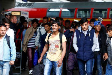 Migrants smile after arriving by train at the main railway station in Munich, Germany September 7, 2015. REUTERS/Michaela Rehle