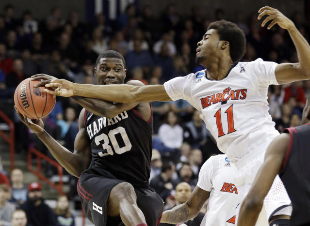Harvard's Kyle Casey (30) tries to hold onto a rebound in front of Cincinnati's Jermaine Lawrence during the first half of a second-round game in the NCAA college basketball tournament in Spokane, Wash., Thursday, March 20, 2014. (AP Photo/Elaine Thompson)