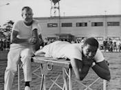 <p>American track and field athlete John Thomas is helped by American team physiotherapist Bill Robertson on the training field at the Summer Olympics.</p>
