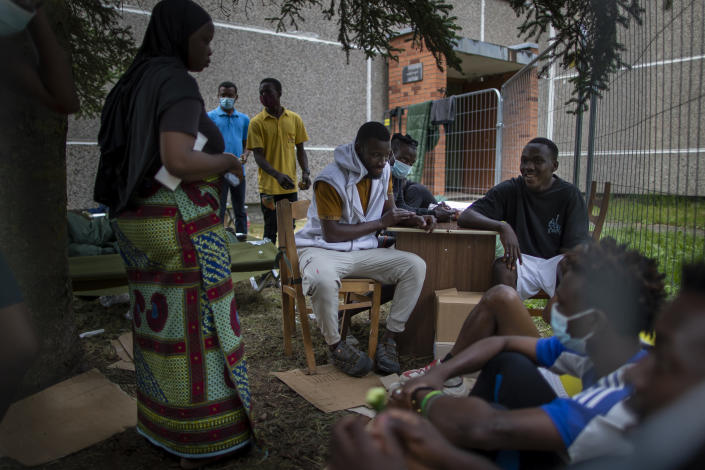 Migrants from Cameroon, Nigeria and Sierra Leone sit outside a school building at the refugee camp at the refugee camp in the village of Verebiejai, some 145km (99,1 miles) south from Vilnius, Lithuania, Sunday, July 11, 2021. Migrants at the school in the village of Verebiejai, about 140 kilometers (87 miles) from Vilnius, haven't been allowed to leave the premises and are under close police surveillance. Some have tested positive for COVID-19 and have been isolated in the building. (AP Photo/Mindaugas Kulbis)