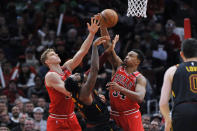 Cleveland Cavaliers' Andre Drummond (3) and Chicago Bulls' Wendell Carter Jr. (34) and Lauri Markkanen (24) vie for a rebound during the second half of an NBA basketball game Tuesday, March 10, 2020, in Chicago. (AP Photo/Paul Beaty)