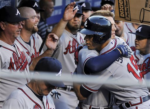 Atlanta Braves' Andrelton Simmons, right, celebrates with Atlanta Braves' Freddie Freeman after Simmons hit a solo home run in the first inning of a baseball game against the Philadelphia Phillies on Saturday, July 6, 2013, in Philadelpia. (AP Photo/Michael Perez)