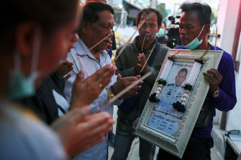 Relatives pay their respects to Captain Siriwiwat Sangprasita (seen in the portrait), a victim of a gun battle involving a Thai soldier on a shooting rampage at a hospital in Nakhon Ratchasima