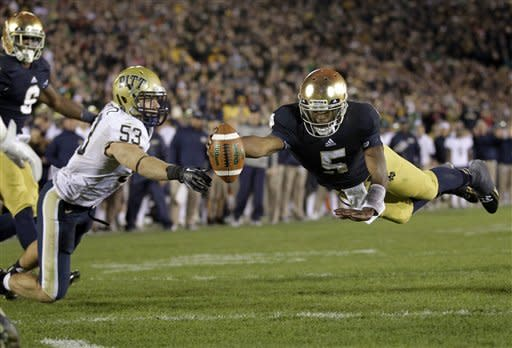 Notre Dame quarterback Everett Golson, right, dives into the end zone in front of Pittsburgh linebacker Joe Trebitz for a two-point conversion to tie the score late in the fourth quarter Pittsburgh of an NCAA college football game in South Bend, Ind., Saturday, Nov. 3, 2012. Notre Dame defeated Pittsburgh 29-26 in triple overtime. (AP Photo/Michael Conroy)