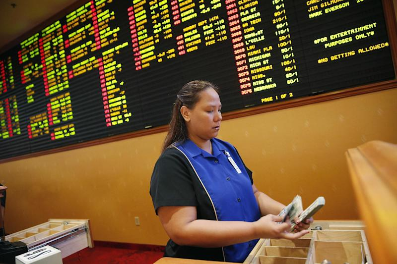 FILE - In this Aug. 20, 2015, file photo, Therese Duenas counts money as she takes bets in the sports book at the South Point hotel and casino in Las Vegas. Las Vegas casinos can't agree on an NCAA tournament favorite, with favorites changing within hours. (AP Photo/John Locher, File)