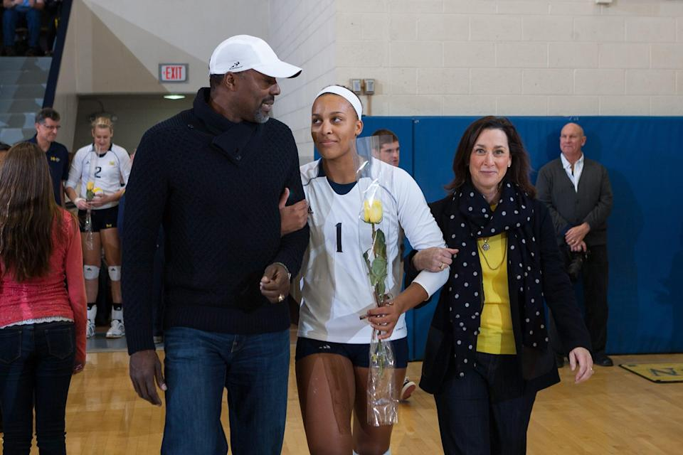 Molly Toon (center) walks onto the court during a Senior Day celebration for the University of Michigan volleyball team on Nov. 27, 2013 with her parents, Al and Jane Toon.