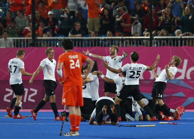 Netherlands' Valentin Verga (front) reacts as Germany's team players celebrate winning during their men's gold medal hockey match at the Riverbank Arena at the London 2012 Olympic Games August 11, 2012. REUTERS/Suzanne Plunkett (BRITAIN - Tags: SPORT OLYMPICS FIELD HOCKEY)