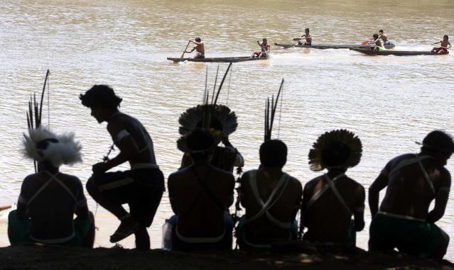 Brazilian indigenous people watch a canoeing competition in the Cuiaba river during the XII Games of the Indigenous People in Cuiaba November 15, 2013. Forty-eight Brazilian Indigenous tribes will present their cultural rituals and compete in traditional sports such as archery, running with logs and canoeing during the XII Games of Indigenous People which will run until November 16. REUTERS/Paulo Whitaker (BRAZIL - Tags: SPORT SOCIETY TPX IMAGES OF THE DAY)