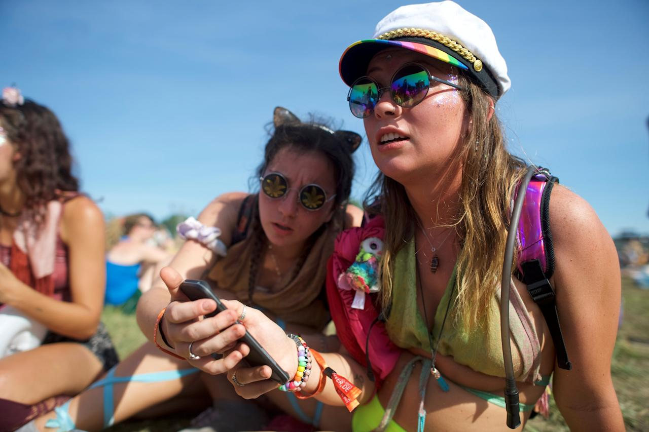 (L-R) Catie Gilbride, 21, and Lizzy  Huggler, 20, converse with friends on the third day of the Firefly Music Festival in Dover, Delaware U.S., June 16, 2018.  REUTERS/Mark Makela