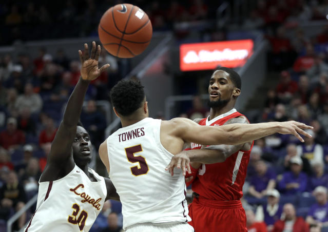 Bradley's Elijah Childs, right, passes around Loyola of Chicago's Aher Uguak (30) and Marques Townes (5) during the second half of an NCAA college basketball game in the semifinal round of the Missouri Valley Conference tournament, Saturday, March 9, 2019, in St. Louis. Bradley won 53-51. (AP Photo/Jeff Roberson)