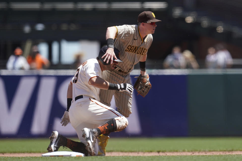 San Diego Padres second baseman Jake Cronenworth, top, looks toward first base after forcing San Francisco Giants' Mike Tauchman, bottom, out at second base on a double play hit into by Wilmer Flores during the first inning of a baseball game in San Francisco, Saturday, May 8, 2021. (AP Photo/Jeff Chiu)