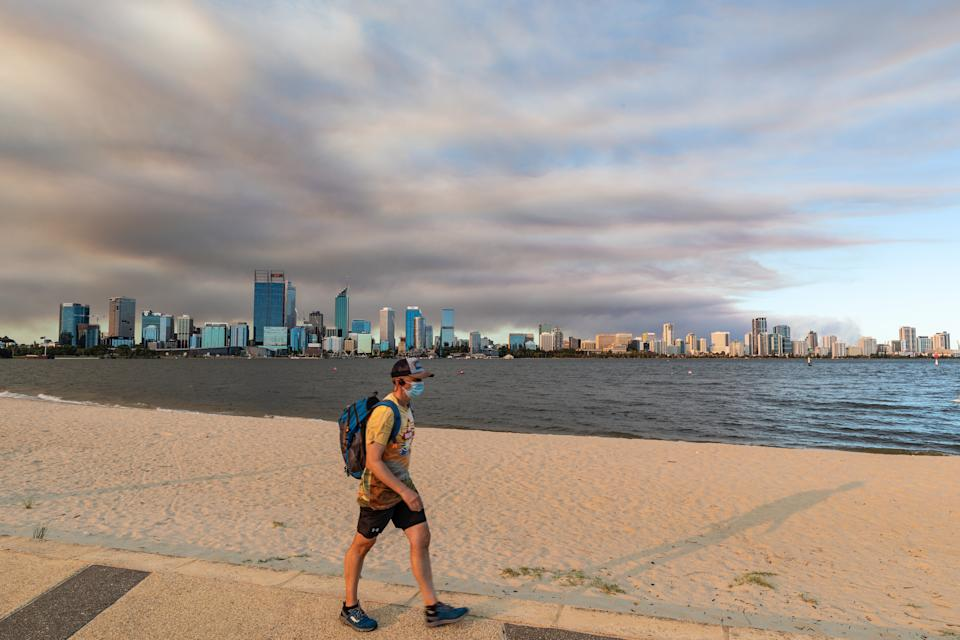 Members of the public exercise on the south Perth foreshore as smoke caused by a bushfire in the Perth hills suburb of Wooroloo rises above the city skyline in Perth.