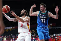 Spain's Ricky Rubio (9) drives to the basket ahead of Slovenia's Luka Doncic (77) during a men's basketball preliminary round game at the 2020 Summer Olympics, Sunday, Aug. 1, 2021, in Saitama, Japan. (AP Photo/Charlie Neibergall)