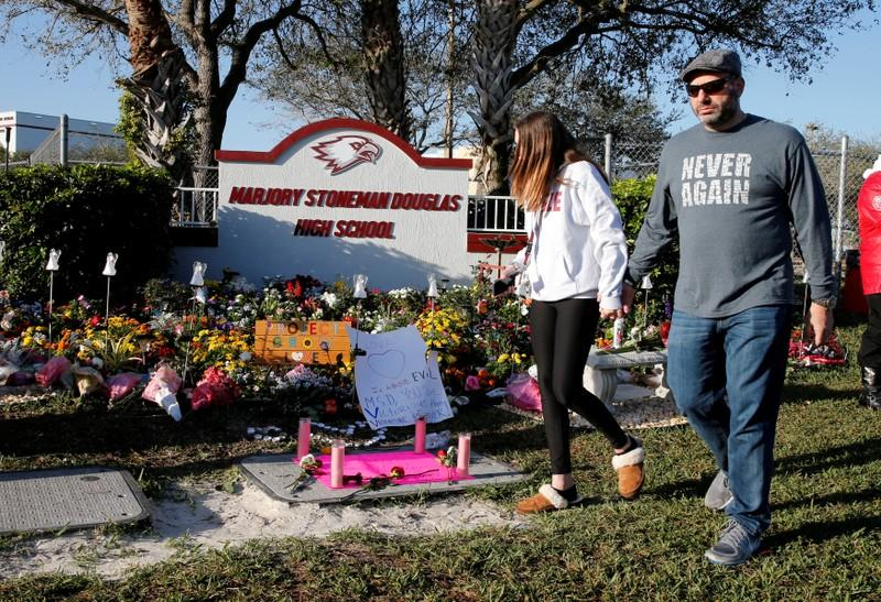 FILE PHOTO: Visitors who asked to not be identified walk past a memorial on the one year anniversary of the shooting which claimed 17 lives at Marjory Stoneman Douglas High School in Parkland