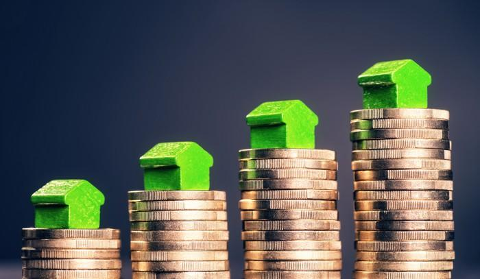Green toy houses on top of rising stacks of gold coins.