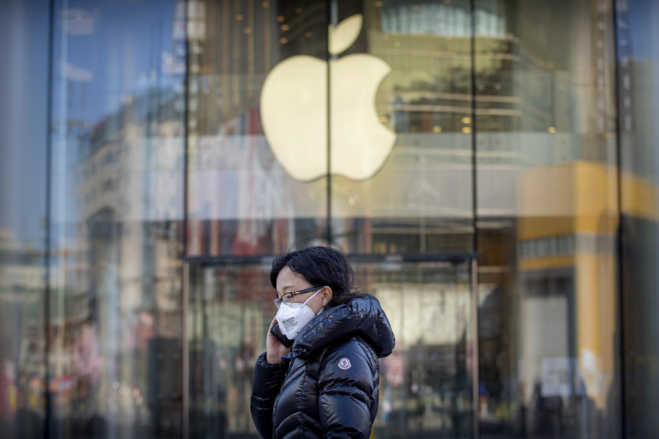 A woman wears a face mask as she walks past an Apple store that is temporarily closed due to health concerns in Beijing, Tuesday, Feb. 4, 2020. Apple announced that it will temporarily close all of its stores in China due to a virus outbreak. (AP Photo/Mark Schiefelbein)