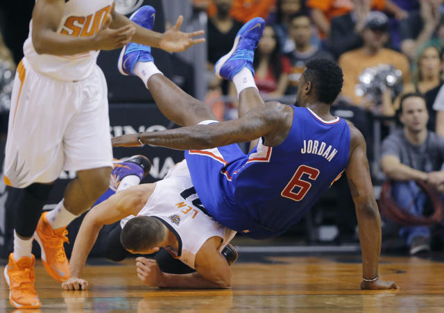 Los Angeles Clippers' DeAndre Jordan (6) falls over Phoenix Suns' Alex Len during the first half of an NBA basketball game, Tuesday, March 4, 2014, in Phoenix. (AP Photo/Matt York)