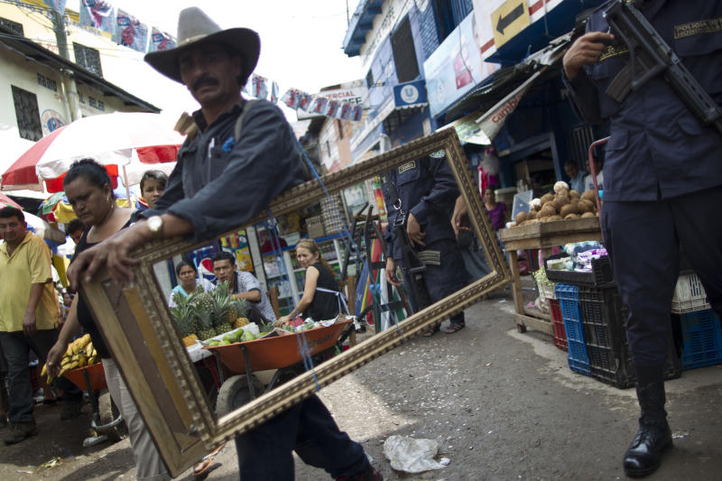 In this June 1, 2013 photo, a National Police officer is reflected in the full-length mirror carried by a street vendor walking through l Mayoreo market in Tegucigalpa, Honduras. In the midst of a scandal over the police shooting of a university president's son, the government of Honduras launched an unprecedented effort last year to clean up a U.S.-backed police force widely seen as deeply brutal and corrupt. By April of this year, the Honduran government said it had dismissed a mere seven members of the 13,800-person force, a vivid illustration of the lack of progress in a year-old effort aided by the U.S. to reform police in a country that's swamped with U.S.-bound cocaine and wracked by one of the world's highest homicide rates. (AP Photo/Esteban Felix)