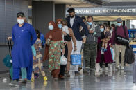 FILE - In this Tuesday, Aug. 31, 2021, file photo, families evacuated from Kabul, Afghanistan, walk through the terminal to board a bus after they arrived at Washington Dulles International Airport, in Chantilly, Va. U.S. religious groups of many faiths are gearing up to assist the thousands of incoming refugees. (AP Photo/Gemunu Amarasinghe)