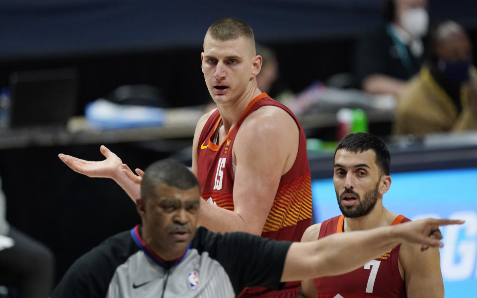 Nikola Jokic argues for a foul as Facundo Campazzo looks on while referee Tony Brothers walks away.