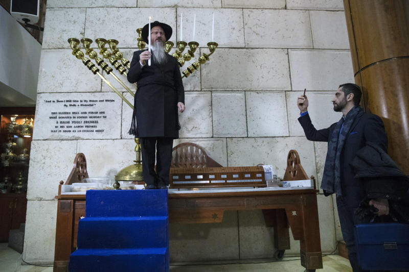 Russia's chief rabbi Berel Lazar, center, lights a Hanukkah candle during the International Holocaust Survivors Night of the Jewish Community at the Jewish Community Centre and Synagogue in Moscow, Russia, Tuesday, Dec. 4, 2018. An international holocaust survivors night was marked in Moscow on Tuesday. The tribute was dedicated specifically to remembering those who survived the terrible events and also took place in New York, Berlin and Jerusalem. Each location was attended by holocaust survivors. (AP Photo/Pavel Golovkin)
