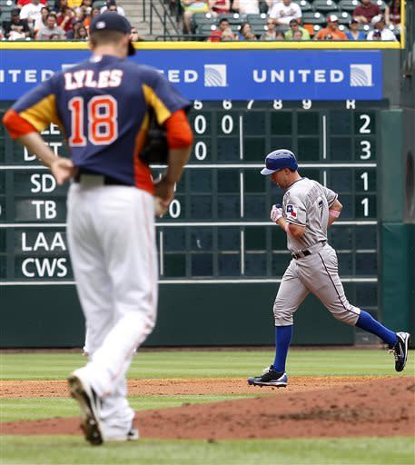 Houston Astros pitcher Jordan Lyles (18) walks back to the mound as Texas Rangers' David Murphy (7) rounds the bases after hitting a two-run home run in the third inning during a baseball game on Sunday, May 12, 2013, in Houston. (AP Photo/Patric Schneider)