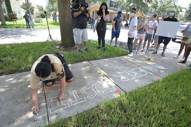 PHOTO: Protester Taylor Dimuzio writes a message with chalk on a sidewalk in front of a townhouse owned by Minneapolis police officer Derek Chauvin, May 29, 2020, in Windermere, Fla. (Phelan M. Ebenhack/AP)